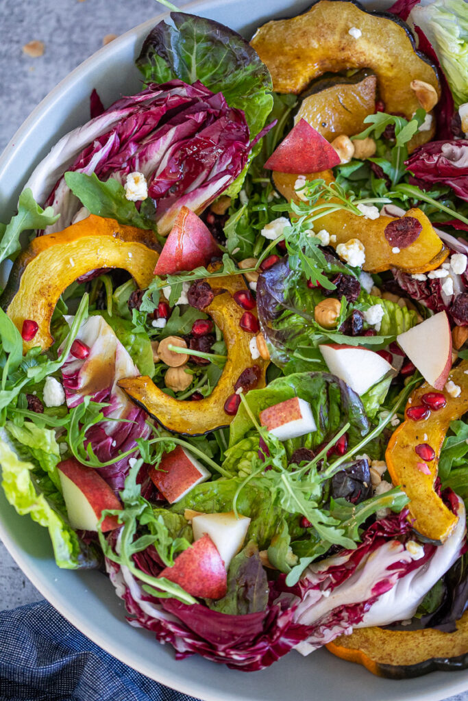 A bright Autuman Roasted Acorn Squash Salad with Maple-Spiced Vinaigrette boasting vivid colors of orange, reds and greens.