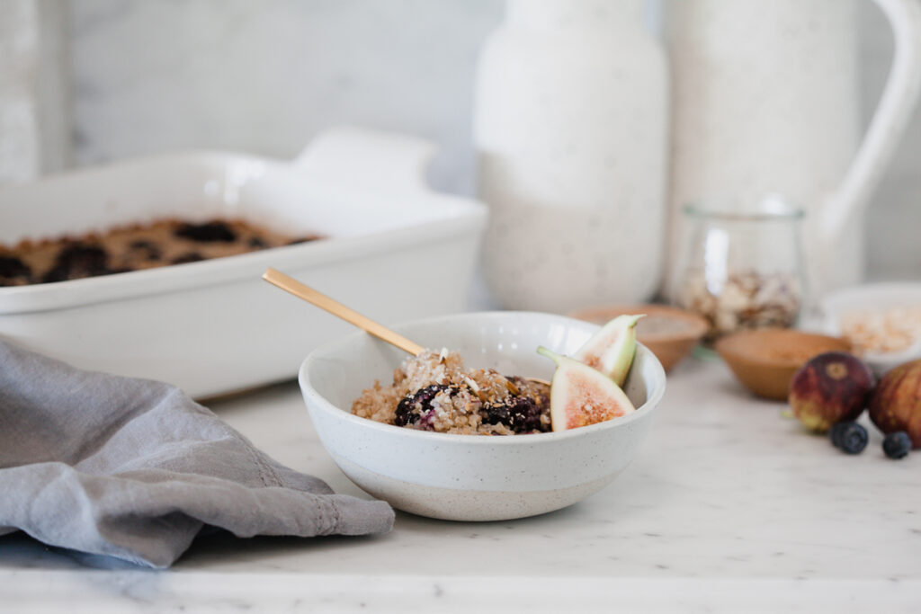 Baked Steel Cut Oatmeal topped with berries and nuts in a white bowl sitting on a kitchen counter next to a casserole dish